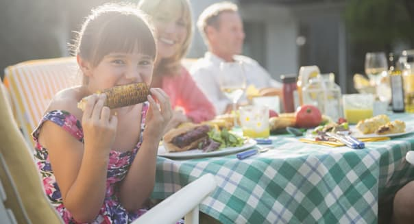 Girl eating corncob at table in backyard