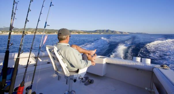 Man sitting in back of sport fishing boat, rear view