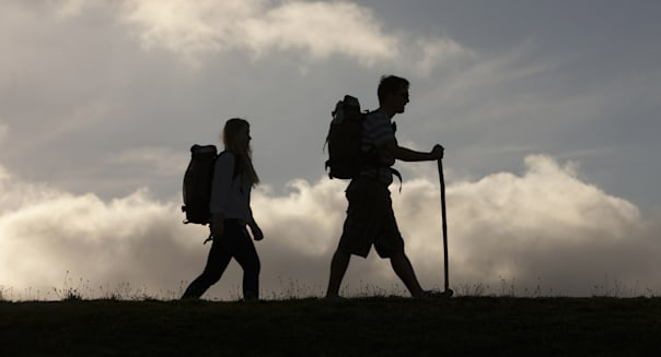 Hikers with backpack and walking stick