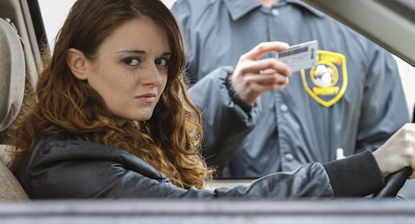 Woman looks into distance after being pulled over, horizontal
