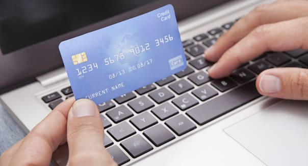 Man Sitting With Laptop And Credit Card Shopping Online