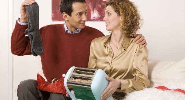 Couple sitting on sofa, holding toaster and socks
