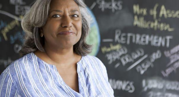 Senior smiling in front of blackboard