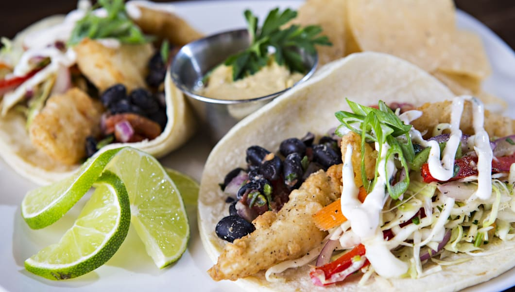 Plate of fish tacos with chips and lime.