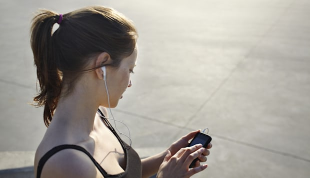 Female runner tjecking results on her smartphone