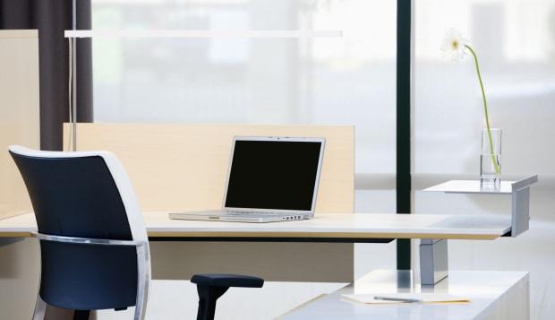 Empty desk with laptop in modern office