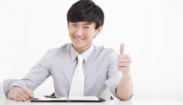 Young businesswoman doing thumbs up