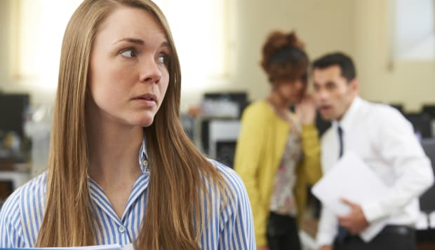 Businesswoman Being Gossiped About By Colleagues In Office