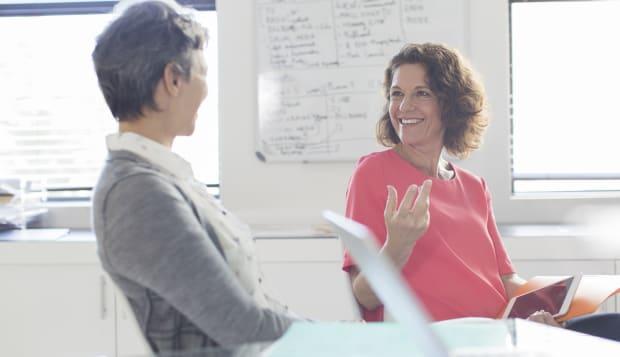 Two smiling women talking in office, whiteboard in background