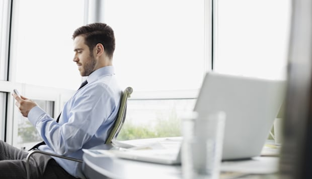 Businessman texting on smart phone