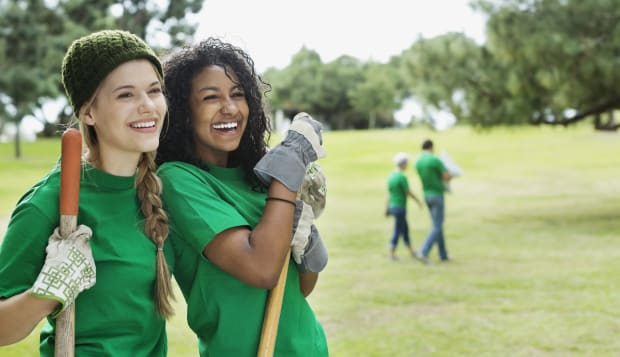 Happy young female environmentalists with shovels looking away in park