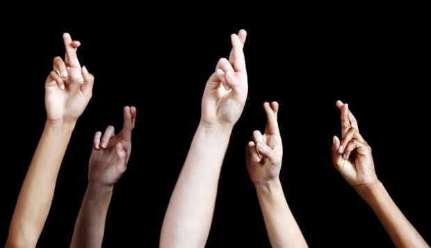 'Five mixed hands are raised against a black background, all with fingers hopefully crossed, averting bad luck.'