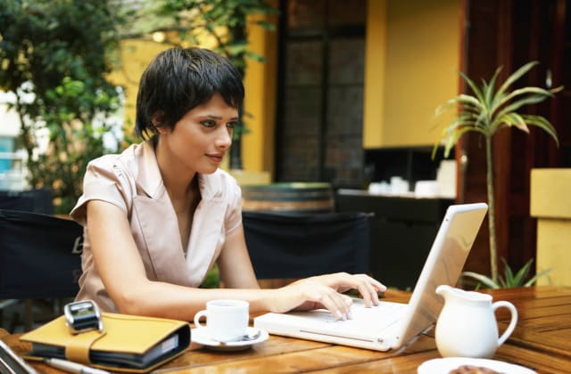 Young woman using laptop while having coffee at restaurant