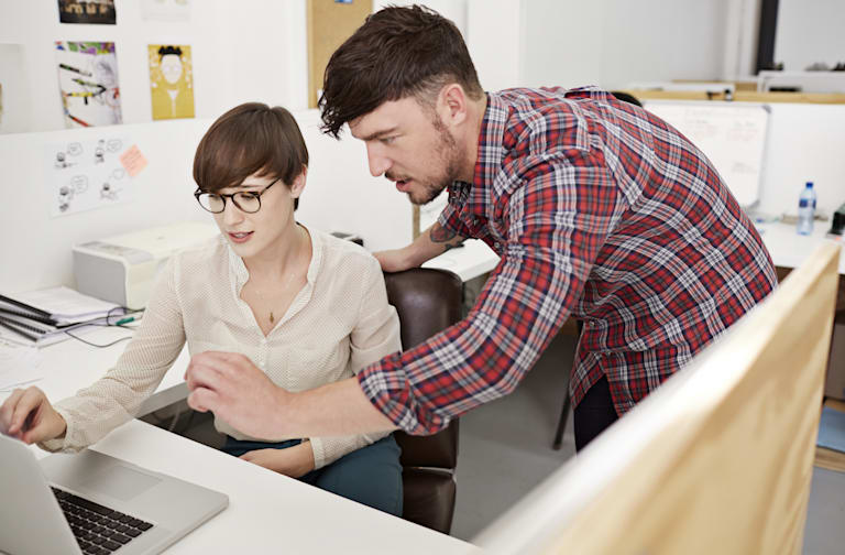 Creative coworkers looking at laptop together