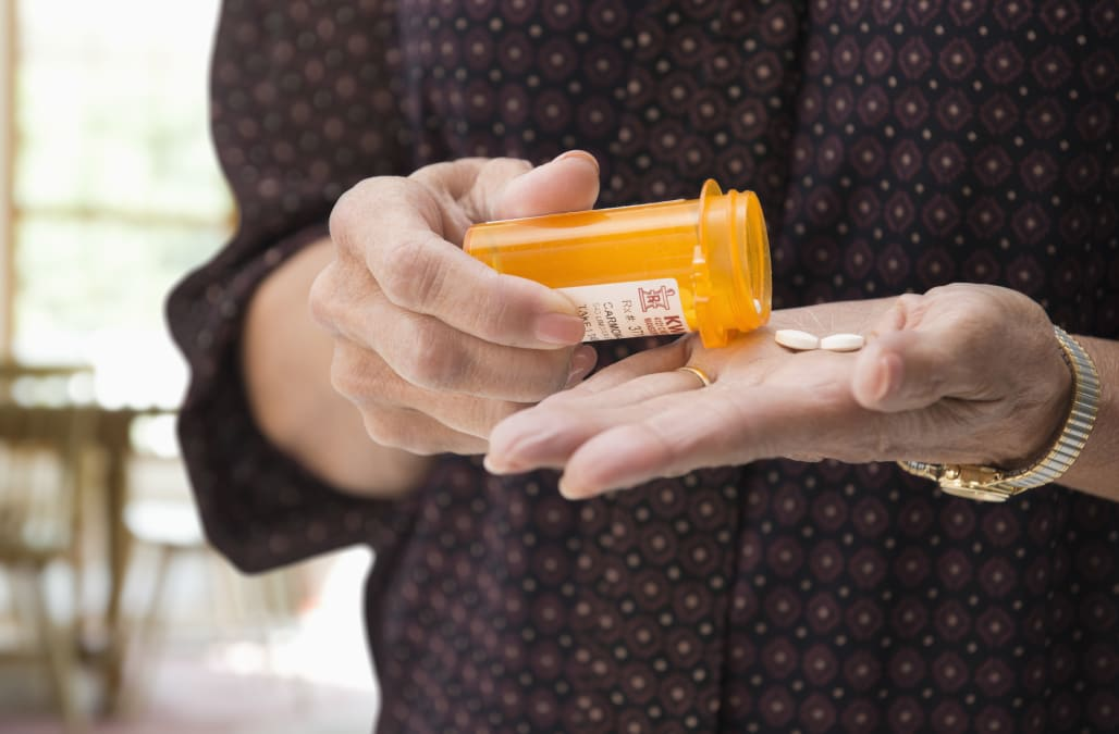 Mixed race woman holding medication pills