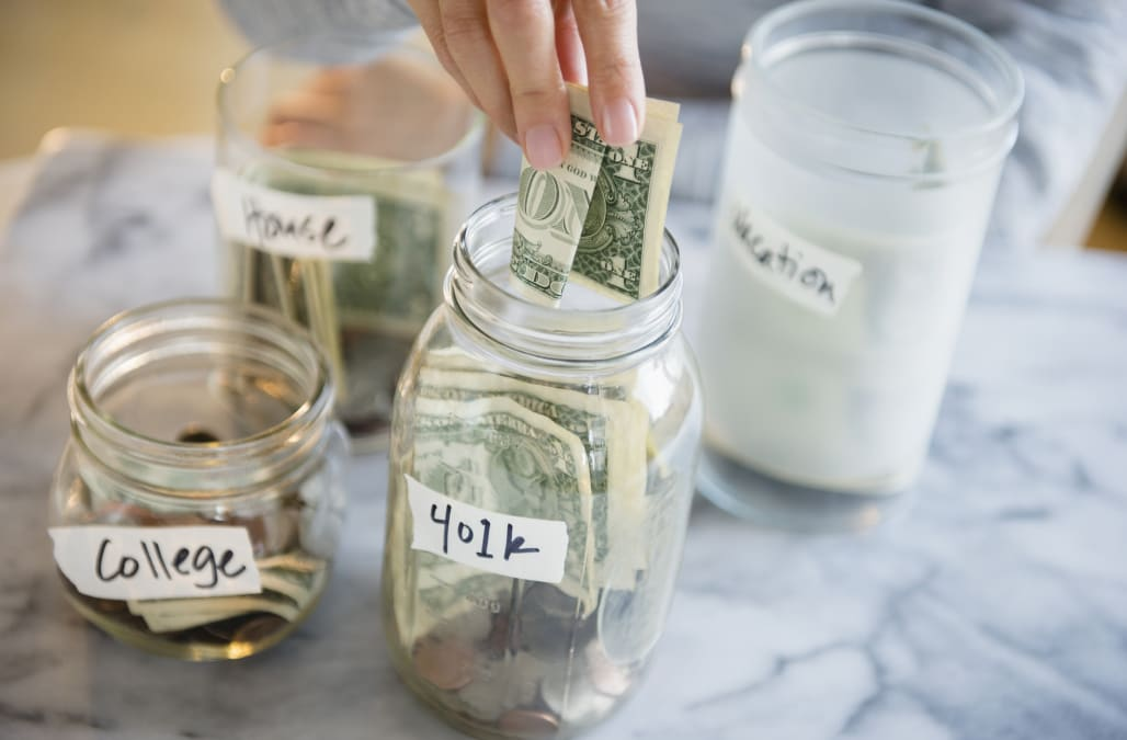 Mixed race woman saving money in jars