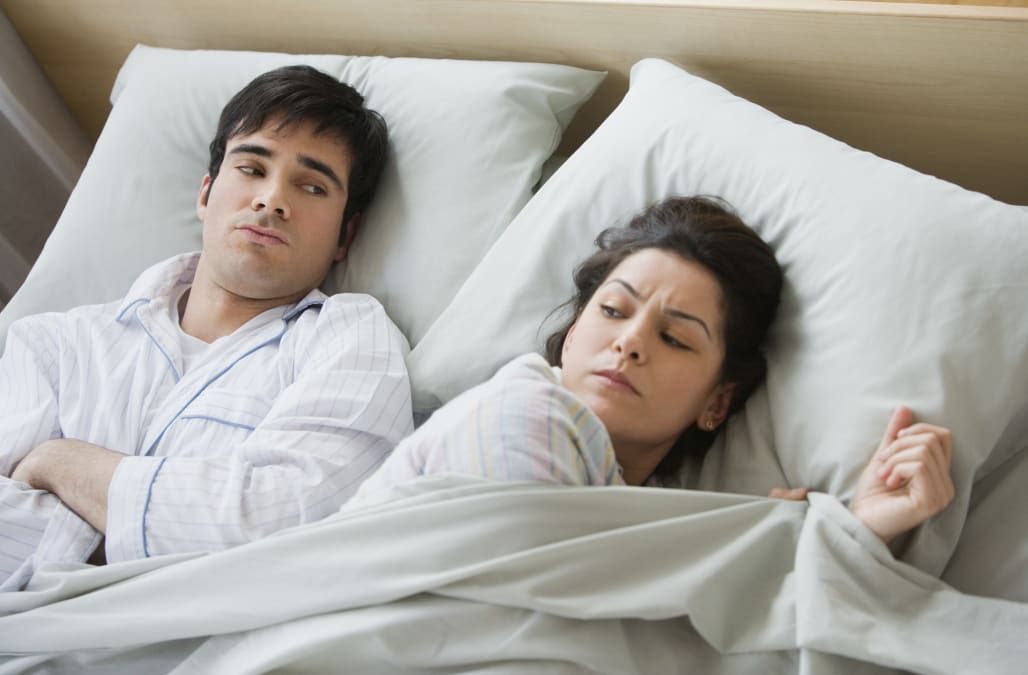 Couple looking angry in bed