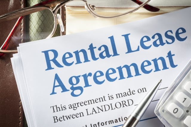 Rental Lease agreement with pen and glasses on desk