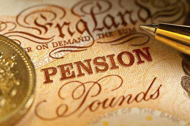 Sterling Pension Savings in the UK. A Ten Pound sterling bank note with a pound coin and a ballpoint pen, with focus on the word