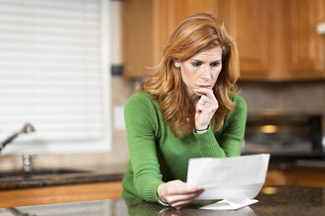 Worried woman reading letter