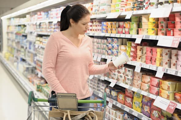 woman reading label on container in supermarket