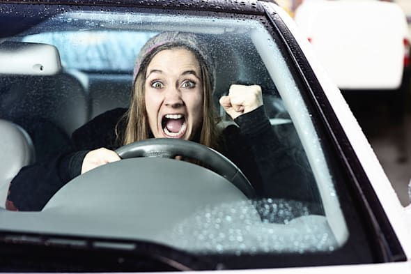 A furiously angry woman driving yells, shaking her fist through the windshield in a bout of road rage!