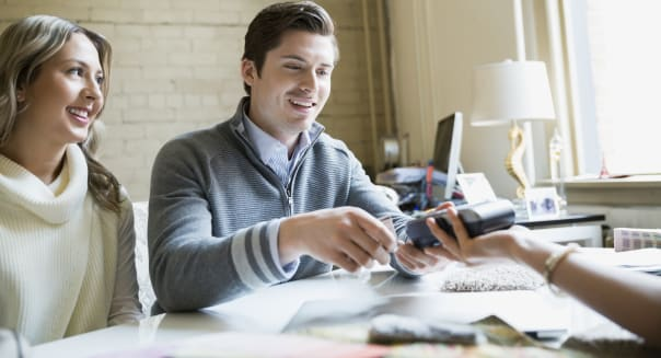Couple paying interior designer with credit card