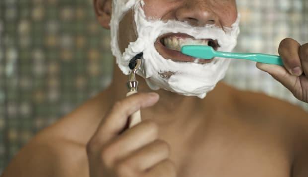 Man Shaving while Brushing His Teeth