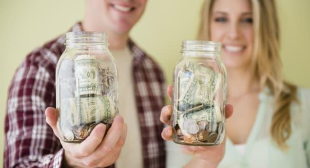 Studio shot of couple holding jars with money