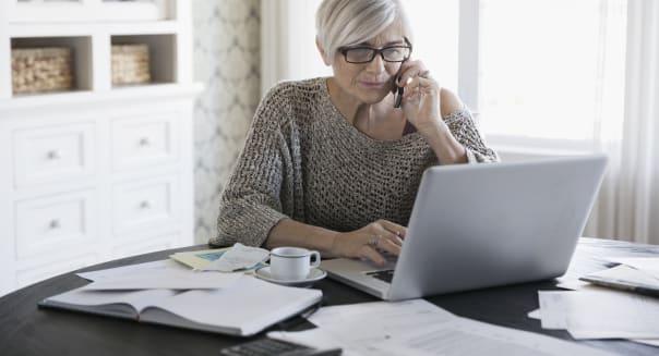 Woman paying bills at laptop talking on telephone