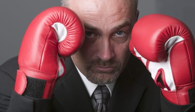 Businessman wearing boxing gloves, portrait, close-up
