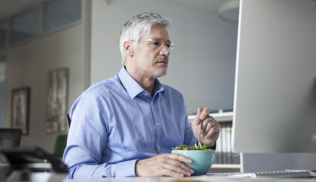 Businessman sitting at desk, eating salad