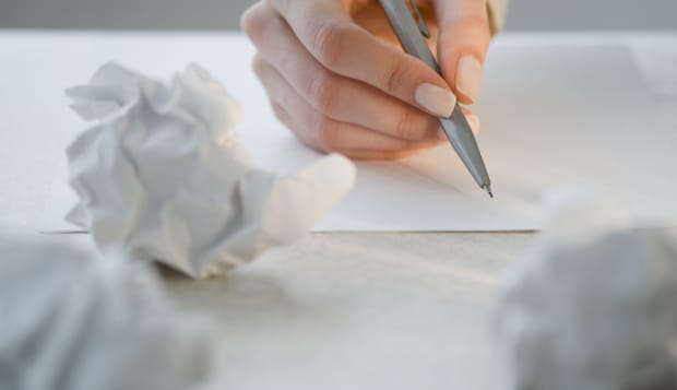 Woman writing next to crumpled papers
