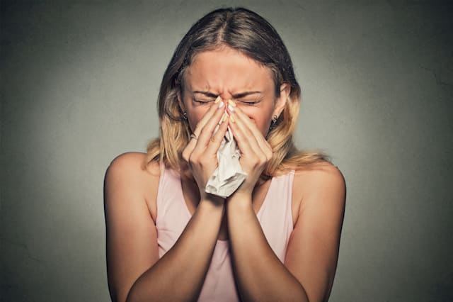 Brunette woman sneezing in a tissue blowing her runny nose