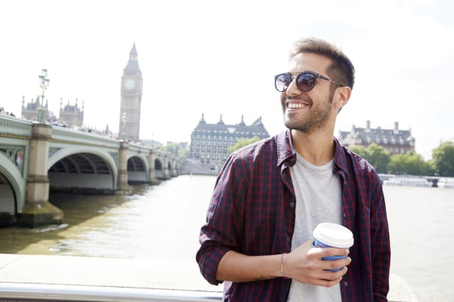 Young man with coffee in London