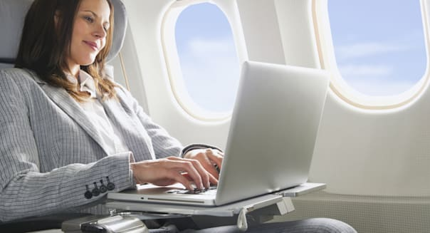Germany, Bavaria, Munich, Mid adult businesswoman using laptop in business class airplane cabin
