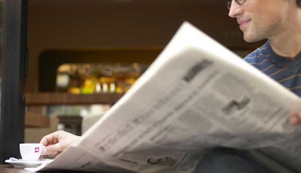 """""""Man sitting at cafe table reading newspaper, reaching for cup"""""""
