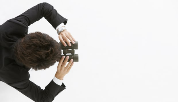 Businessman looking through binoculars, view from above, studio shot