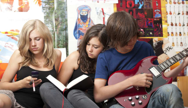 Three teenagers sitting side by side with cell phone, book and guitar