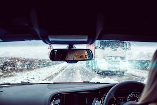Woman driving car in snow