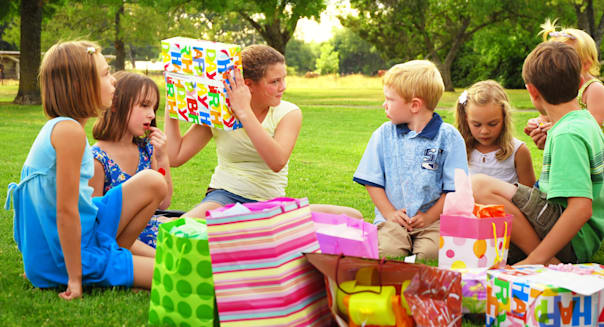 Adolescent girl shakes a gift during her birthday party