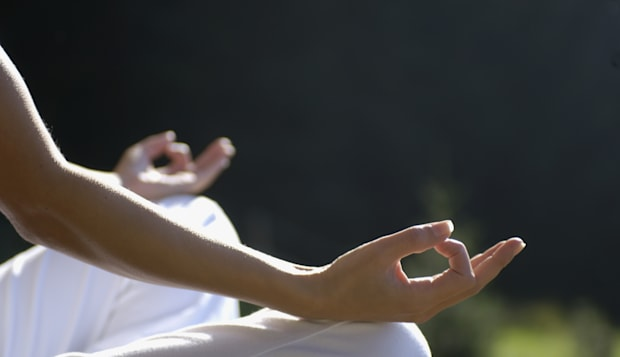 Woman sitting in meditating position outdoors, close-up