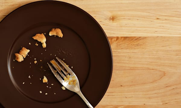 Holiday background image of all that remains of a delicious piece of pumpkin pie.  Plate with crumbs and used fork on wood backg