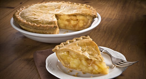 slice of apple pie with whole pie in background