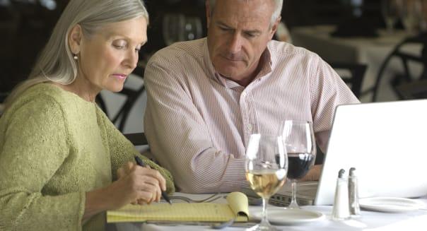 Senior caucasian couple working in cafe.