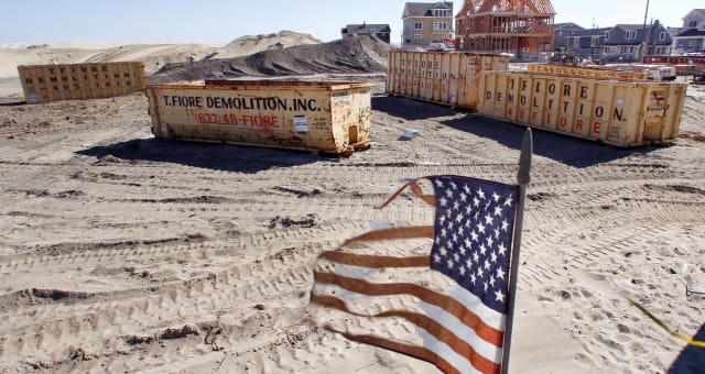 Superstorm Then And Now (This Oct. 13, 2013 photo shows a tattered flag flaping in the wind in Brick, N.J., where 60 small bunga