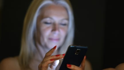 Mature woman in bed browsing mobile phone