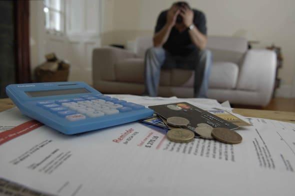 AY7AXR man holds head in hands, credit cards bills money for debt money; dept; credit; crunch; calculator; bills; payments; phon