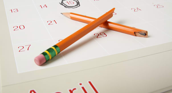 BY47FM Desktop photo with a calendar showing April 15th circled and a broken pencil symbolizing frustration with income taxes. t