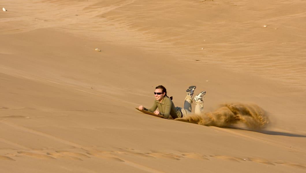 Sandboarding on sand dunes near Swakopmund, Namibia